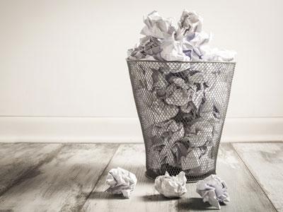 Überquillender Papierkorb mit zerknüllten Blättern