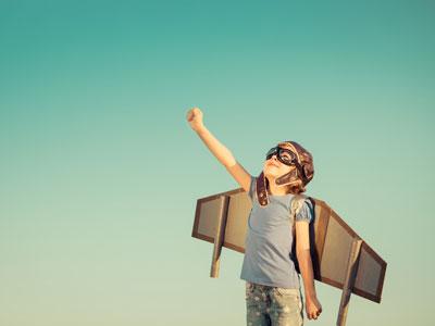 Junge mit Pappflügeln und Fliegerbrille deutet Flug an
