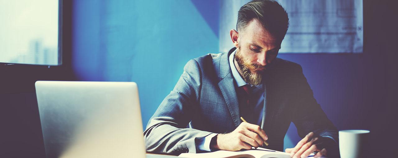 Mann nutzt Flexible Learning am Schreibtisch mit Laptop und Notizblock