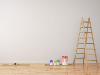 Holzleiter mit Farbeimern daneben vor einer grauen Wand