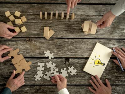 Dienstleistungen: Hände von Seminarteilnehmenden setzen verschiedene Bausteine zusammen