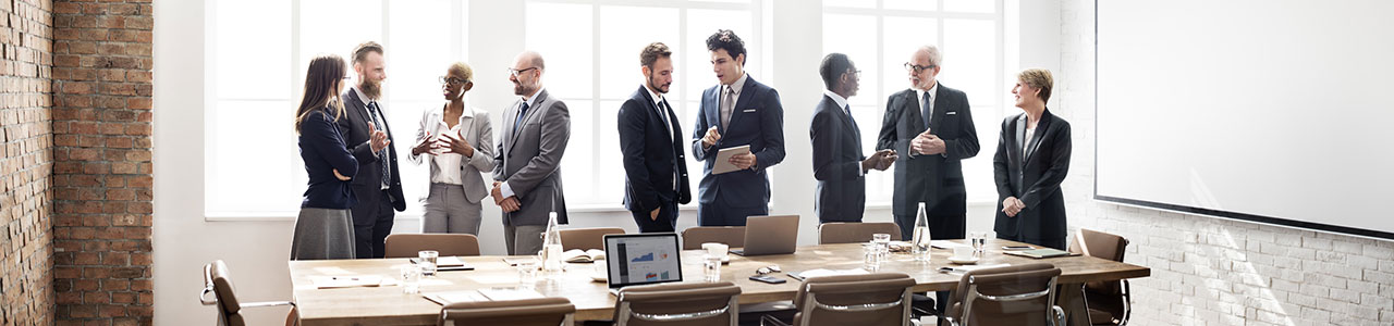 Teilnehmende stehen während einer Pause im Seminarraum und diskutieren
