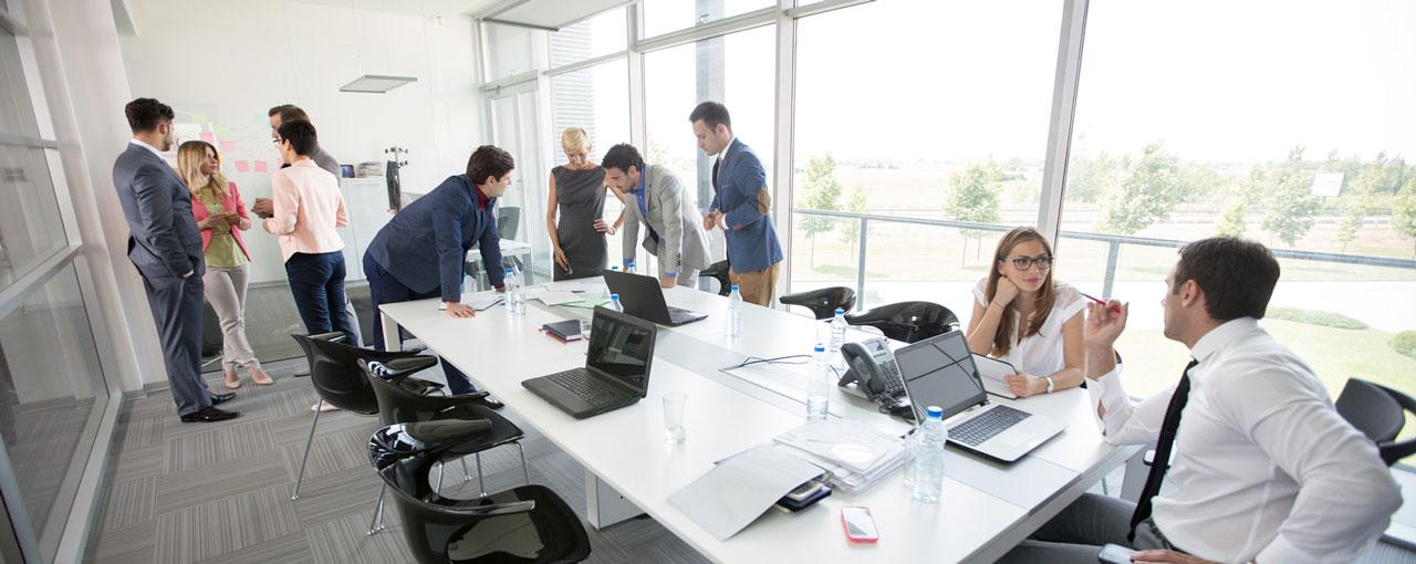 Mitarbeiter in Gruppen um einen großen Tisch verteilt