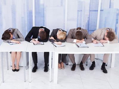 Seminarteilnehmende an Tischreihe sitzend auf ihren Unterlagen eingeschlafen