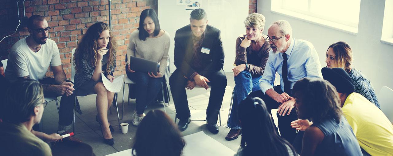 Teilnehmende von Seminaren sitzen im Kreis und diskutieren