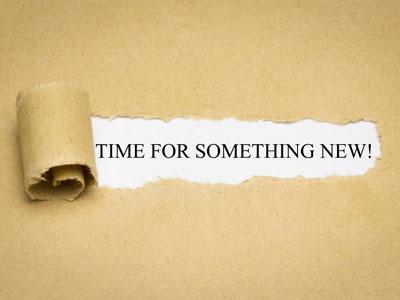 """Einriss auf Papier ermöglicht Sicht auf Aufschrift: """"Time for something new!"""""""