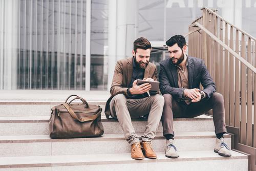 Zwei junge Männer sitzen auf einer Treppe und nutzen Flexible Learning auf einem Tablet