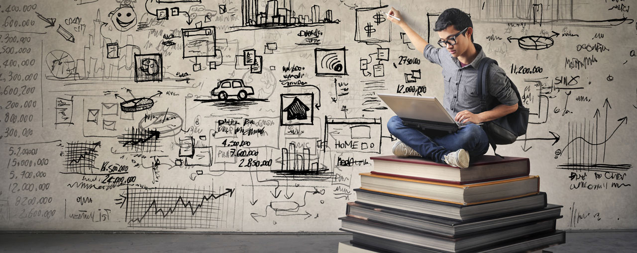 Mann sitzt auf großem Bücherstabel und schreibt auf die Wand