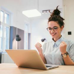 E-Learning: Frau freut sich am Laptop über Lernerfolg