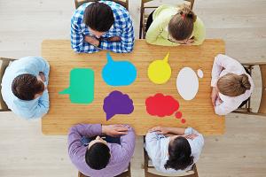 Priorisieren von Aufgaben in Projekten: Menschen um einen Tisch versammelt
