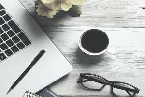 Tisch mit Laptop, Brille und Kaffeetasse