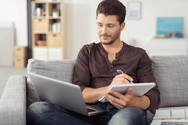 Mann sitzt mit Laptop und Schreibblock auf der Couch und lernt