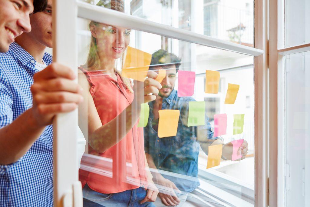 Anforderungsermittlung. Team notiert kreative Ideen auf bunten Zetteln auf einer Transparenten Scheibe im Start-Up Workshop