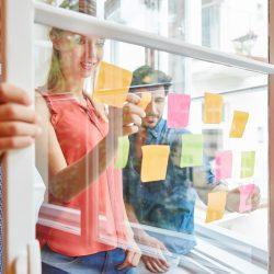 Team notiert kreative Ideen auf bunten Zetteln auf einer Transparenten Scheibe im Start-Up Workshop